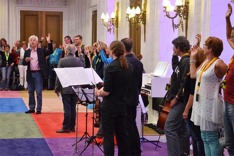 Bach-expert Wim Thijs roept het publiek op de zaal te verlaten met de arm geheven, aan het handje van ons aller muzikale vader Bach